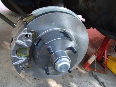 ABS Power Brake Conversion Kit for 1968 Ford Mustang 6 Cylinder, 4 Lugs Wheel. New Left Disc Brake Caliper Installed On Adapter Plate.
